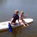 Kinder auf einem Surfbrett im See